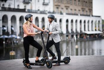 A man and a woman on Segway Ninebot Kickscooter MAXs.