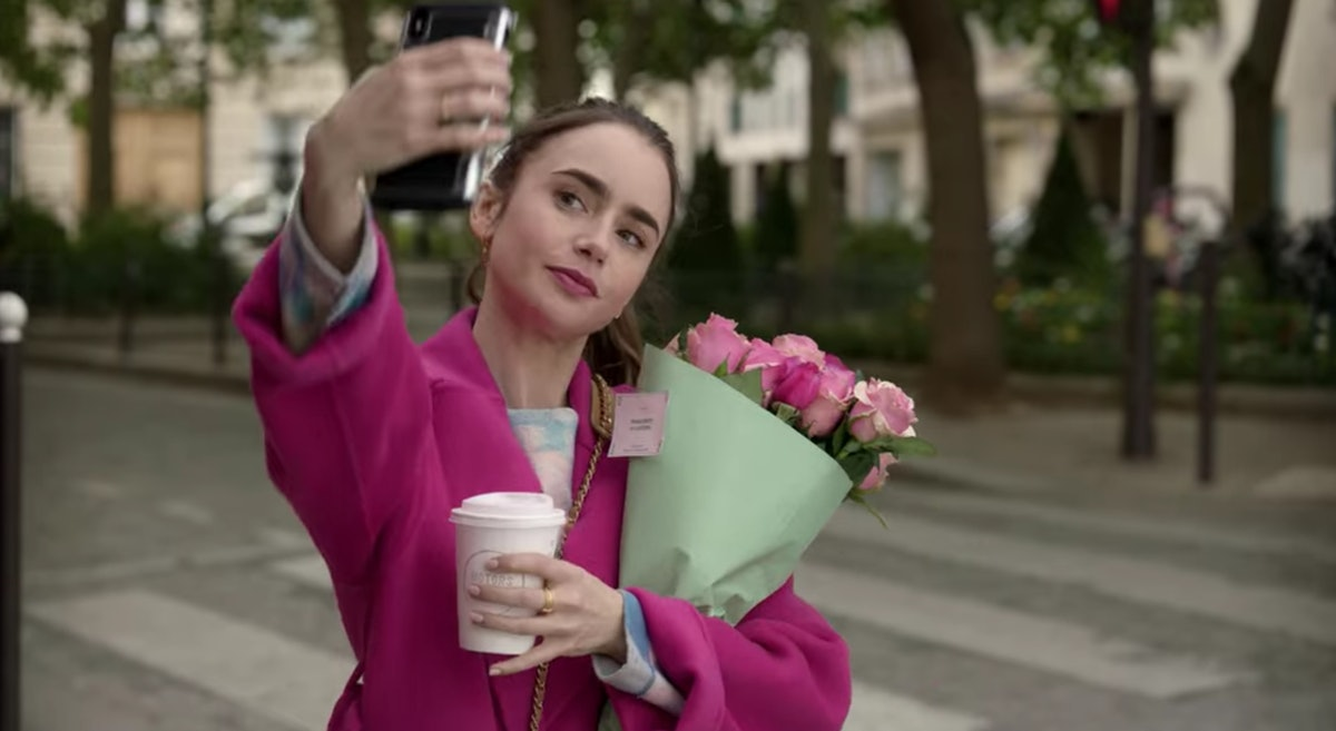 Emily (Lily Collins) poses for a selfie with a bouquet of roses in Paris.
