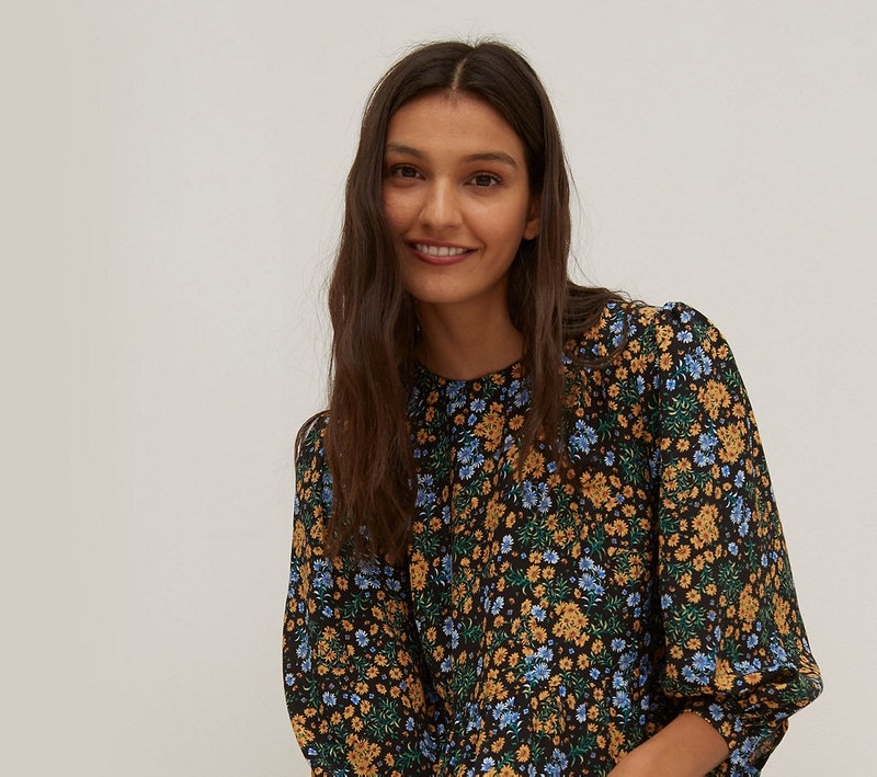 A model wearing a black, blue green and mustard floral dress