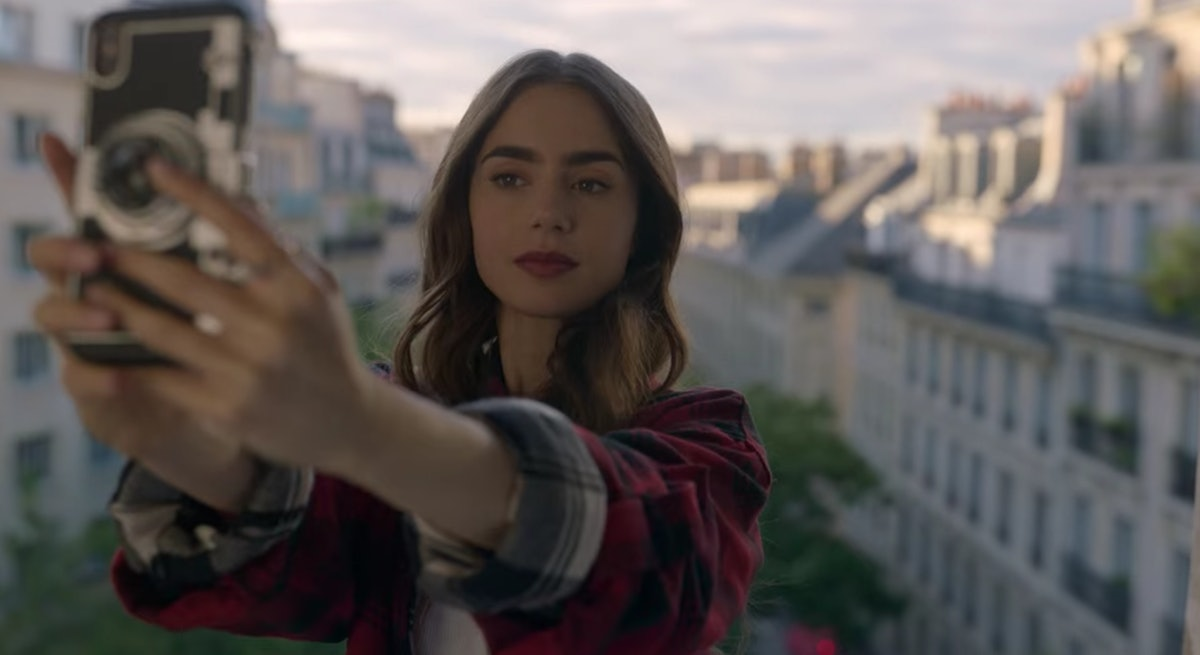 Emily (Lily Collins) stands in front of her balcony, overlooking Paris.
