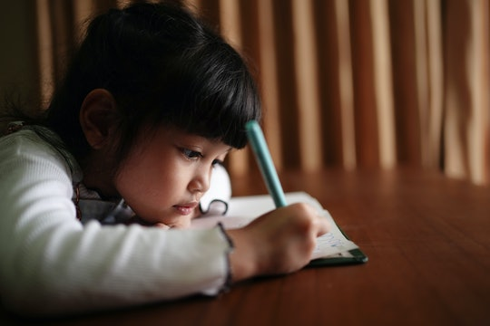 little girl doing schoolwork at home