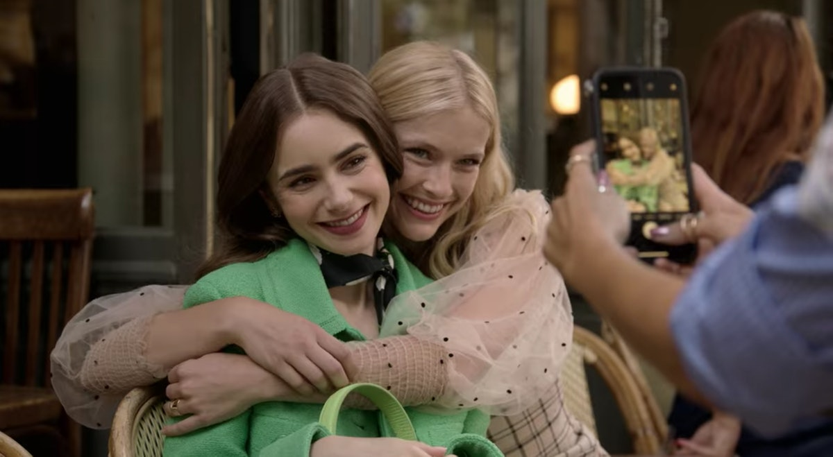 Emily (Lily Collins) poses with Camille (Camille Razat) for a picture while sitting in a Paris cafe.
