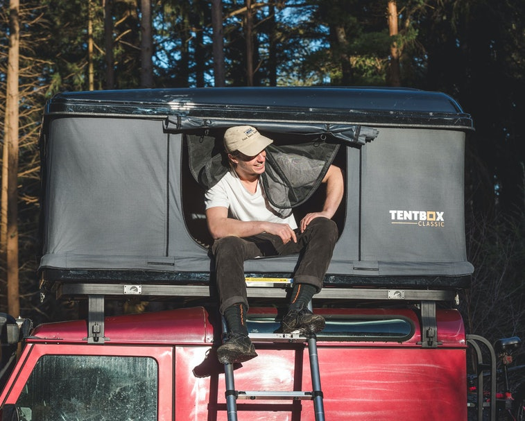 A person sits in a TentBox Classic with their feet on the ladder