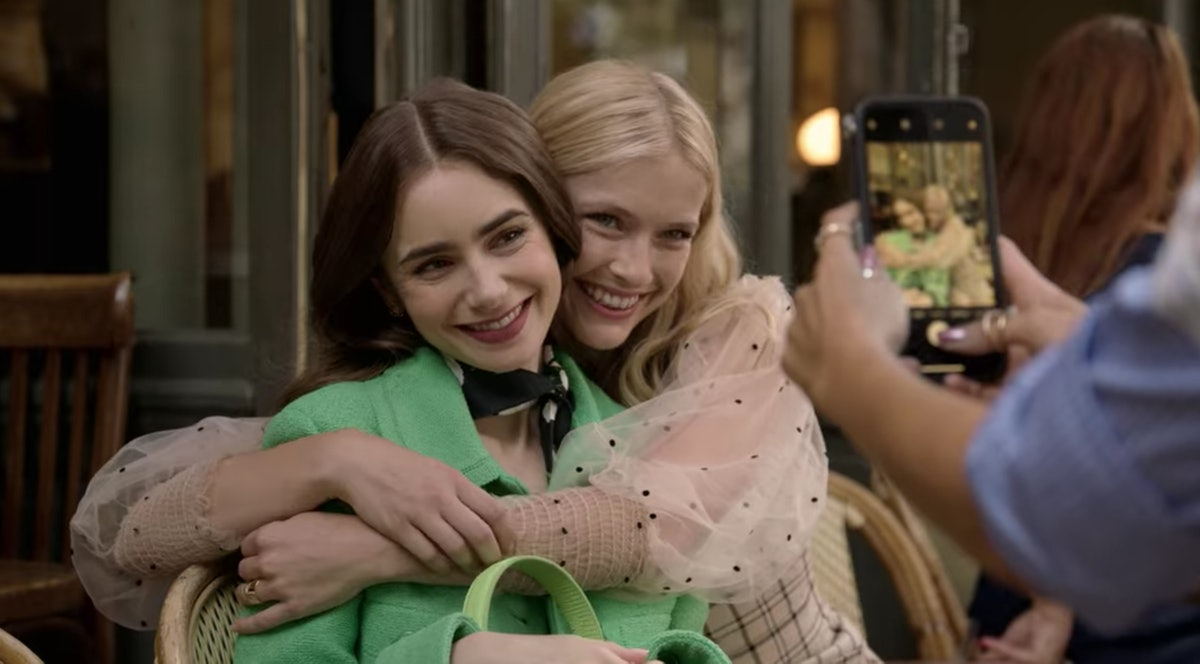 Emily (Lily Collins) and Camille (Camille Razat) hug each other for a picture, while sitting in a cafe in Paris.