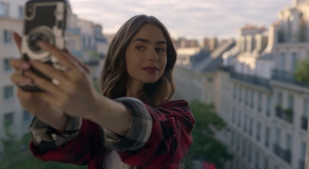 Emily (Lily Collins) takes a selfie while standing in front of her apartment window.