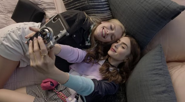Emily (Lily Collins) and Camille (Camille Razat) pose for a selfie while lying in bed.
