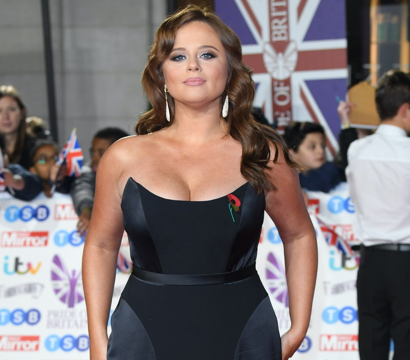 Emily Atack on the red carpet in a navy sleeveless dress with her hair in loose waves