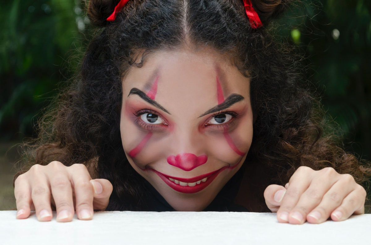 Young woman in evil clown makeup