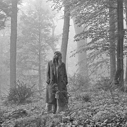 Taylor Swift on the cover of folklore, a moody black and white image of a forest in which swift can be seen wearing a full-length dress under a checked coat