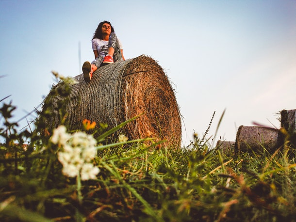 Young woman with hay bale