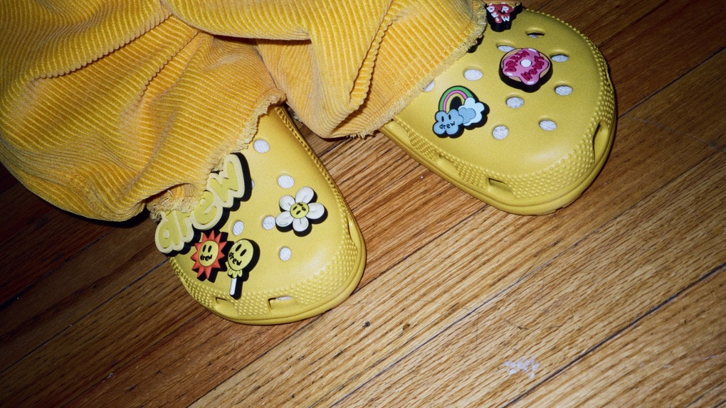 A person wearing a pair of yellow Crocs from the Justin Bieber x Crocs Collaboration