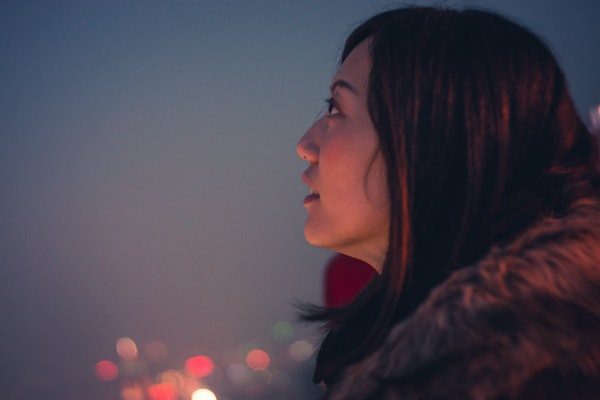 Young woman looking up at night sky