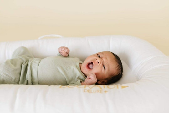 An image of a tiny newborn baby in a white Dock A Tot lounger.