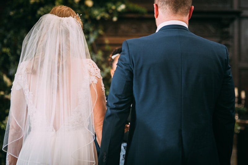 A picture of a person in a wedding dress and a person in a suit, holding hands at the alter