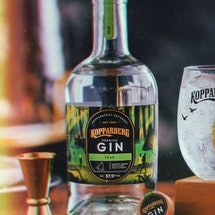 A bottle of kopparberg pear gin on a wooden table next to a spirit measure and a cold glass of fizzy liquid