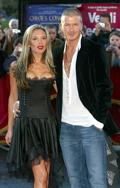 Victoria Beckham wearing a black corset dress with long blonde-highlighted hair and David Beckham wearing a black velvet jacket, white shirt and blue jeans, with a shaved head.