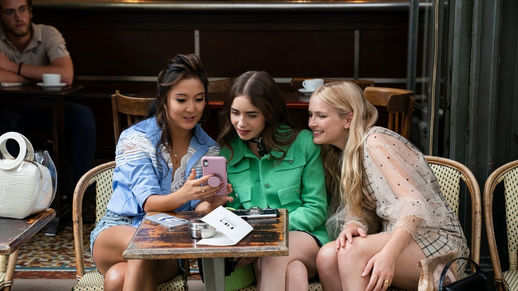 Emily, Mindy, and Camille from 'Emily in Paris' sit at a table at a chic outdoor restaurant in Paris while looking at Mindy's phone.