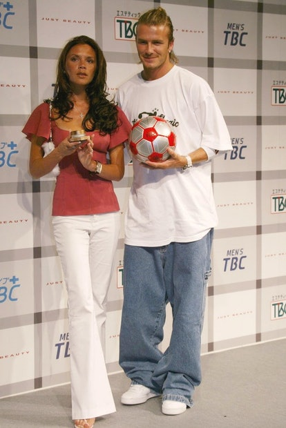 Victoria Beckham wearing white trousers and a red top, David beckham in a baggy white t shirt and baggy blue jeans