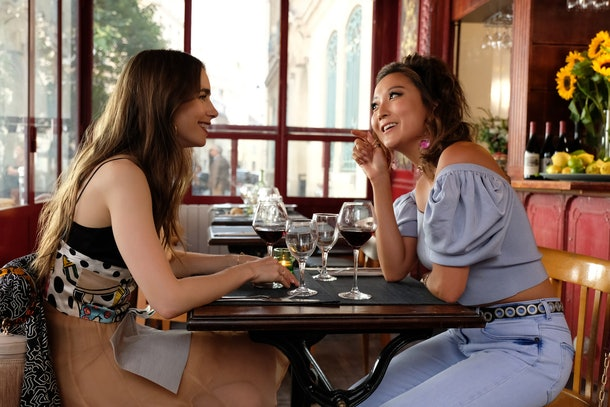 Emily and Mindy from 'Emily in Paris' enjoy dinner and red wine at a restaurant in Paris.