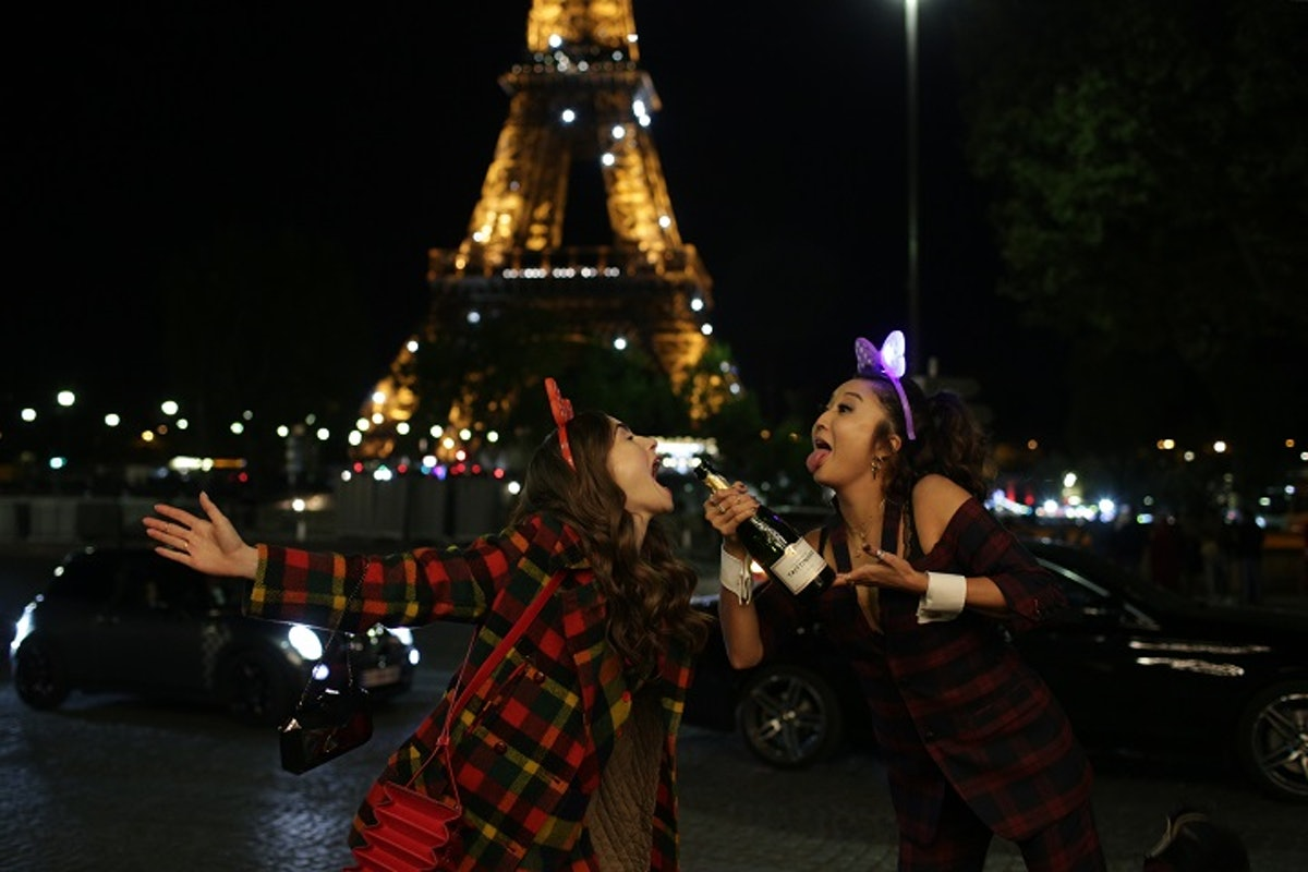 Emily and Mindy from 'Emily in Paris' wear plaid and make silly faces while holding a champagne bott...