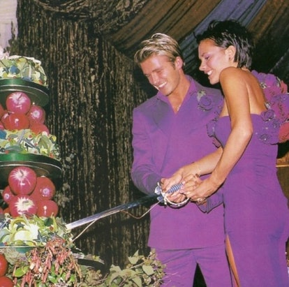 David and Victoria Beckham dressed in royal purple outfits cutting their wedding cake