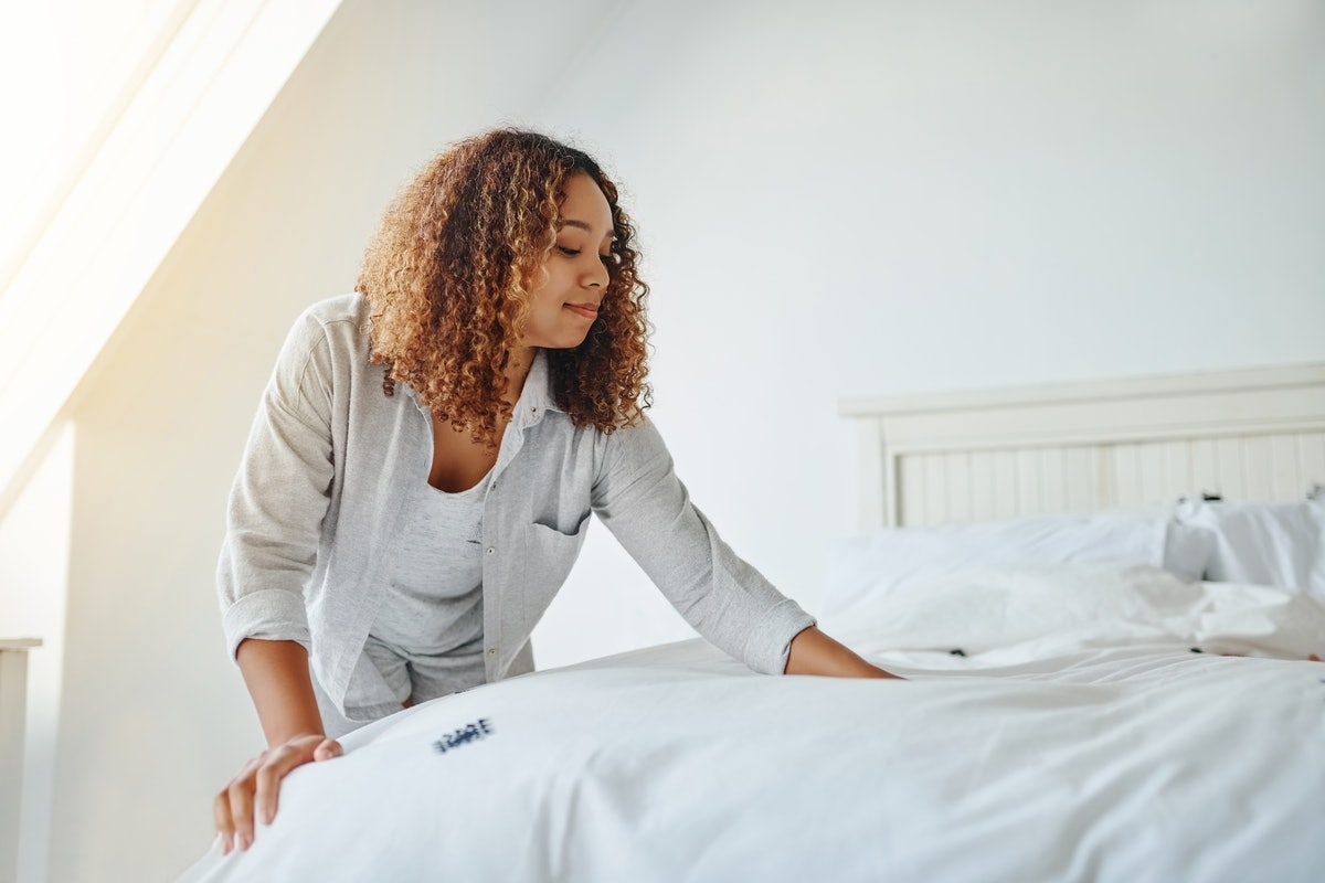 Young woman making her bed