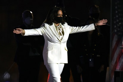 Vice President-elect Kamala Harris wears a white suit, a black mask, and her arms are spread out wid...