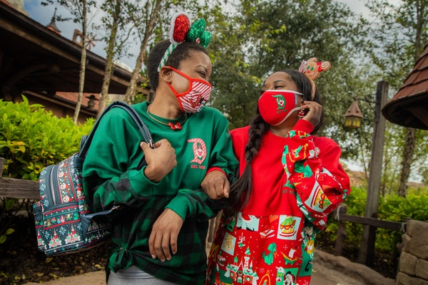 Two sisters wearing Disney Parks holiday merchandise laugh at Disney World.