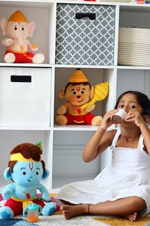 A little girl drinks tea in front of a bookshelf containing Modi Toys' plush Baby Ganesh, Baby Hanuman, and Baby Krishna