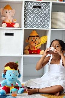 A little girl drinks tea in front of a bookshelf containing Modi Toys' plush Baby Ganesh, Baby Hanuman, and Baby Krishna