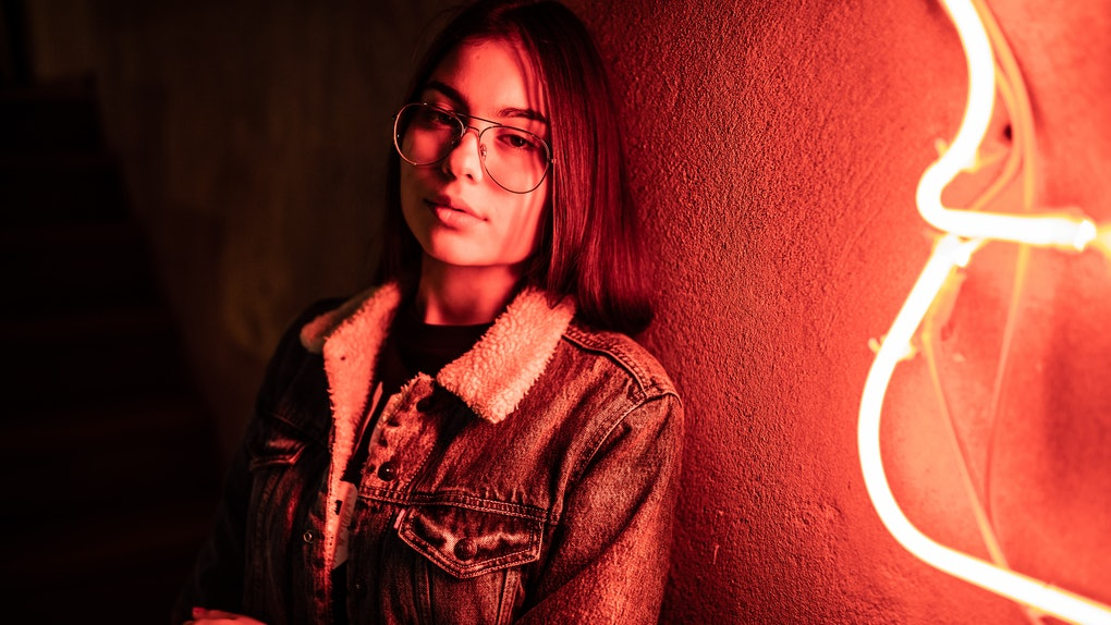 Young woman next to neon light