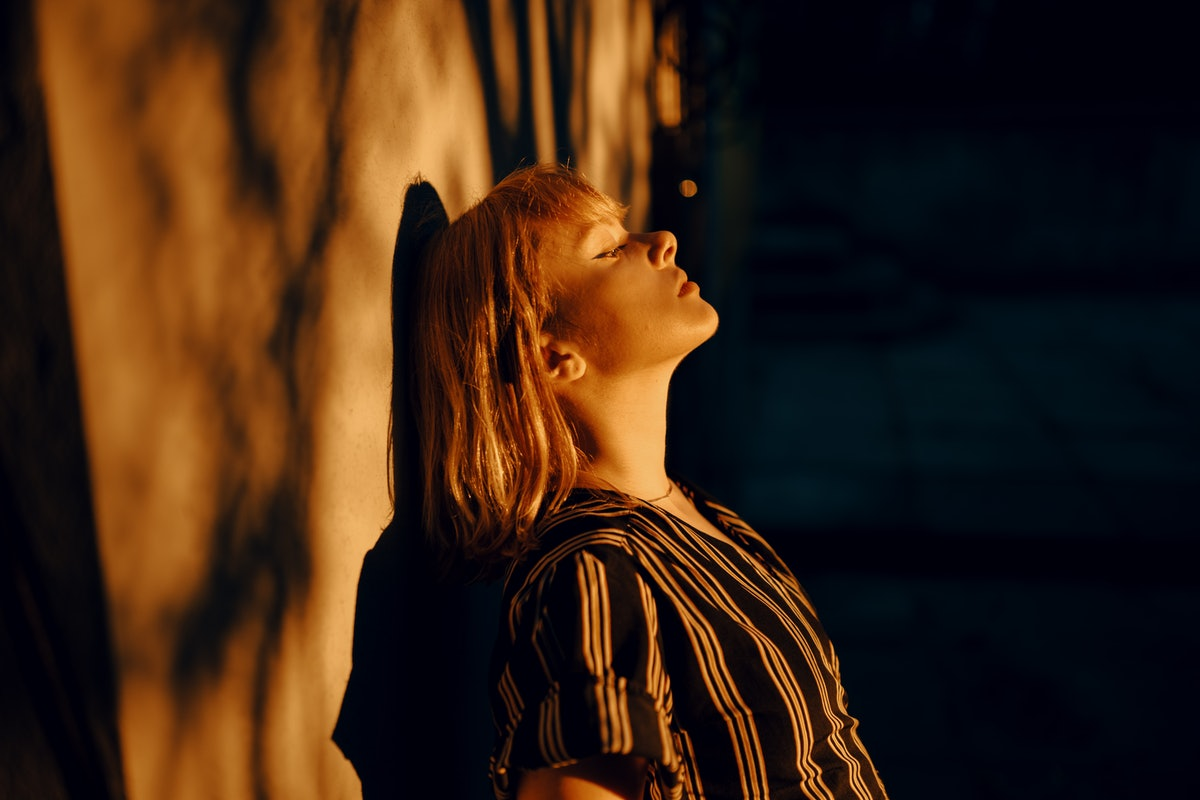 Shadowed portrait of young woman in golden hour