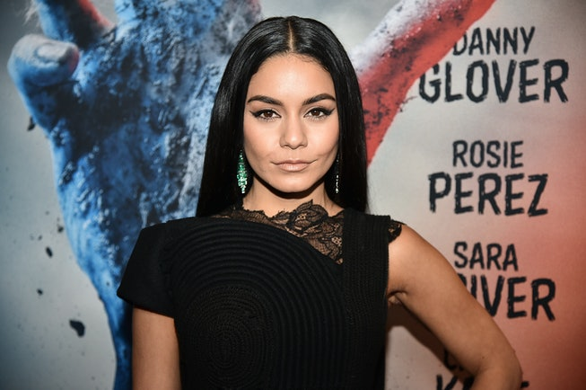 Vanessa Hudgens, with long brown hair that's parted down the middle, poses in a black dress on a red carpet.
