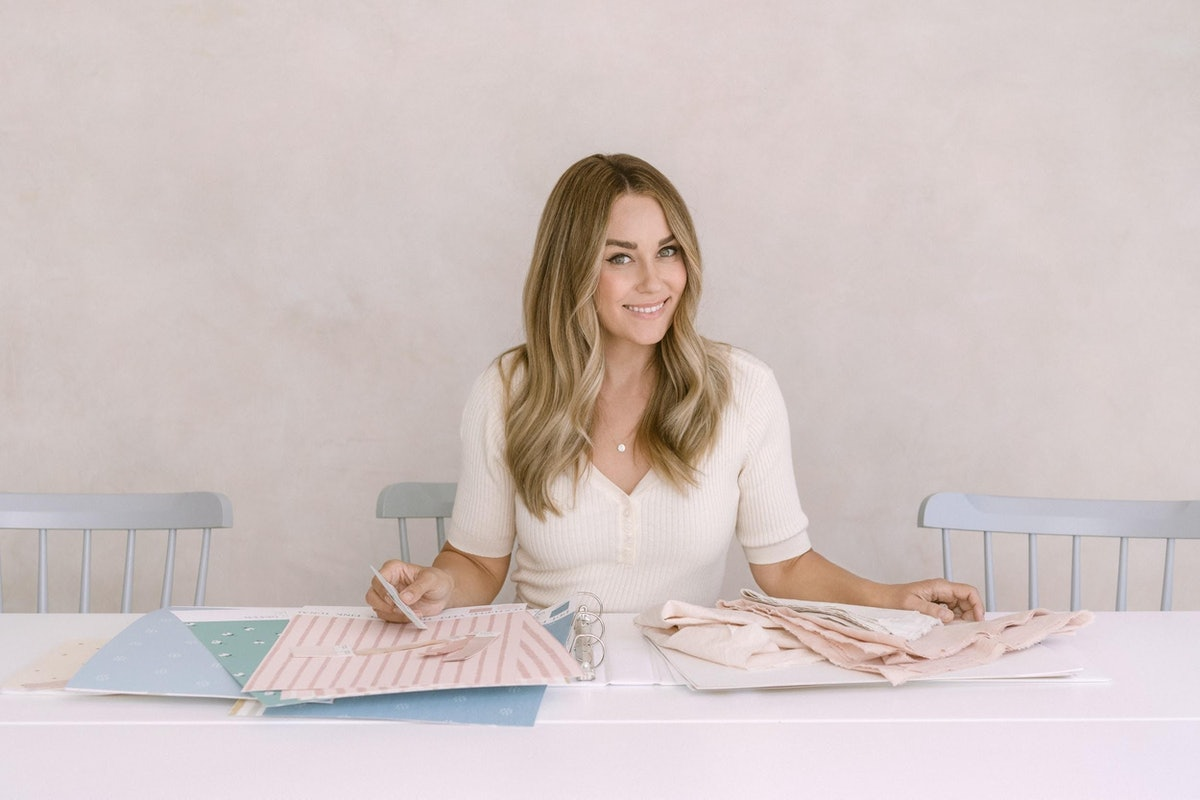 Lauren Conrad sits at a table with some fabric and pattern swatches.
