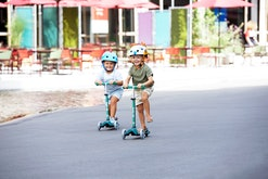Two kids in helmets on Micro Kickboard scooters, riding down the street