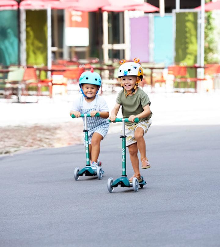Two kids in helmets on Micro Kickboard scooters, riding down the street