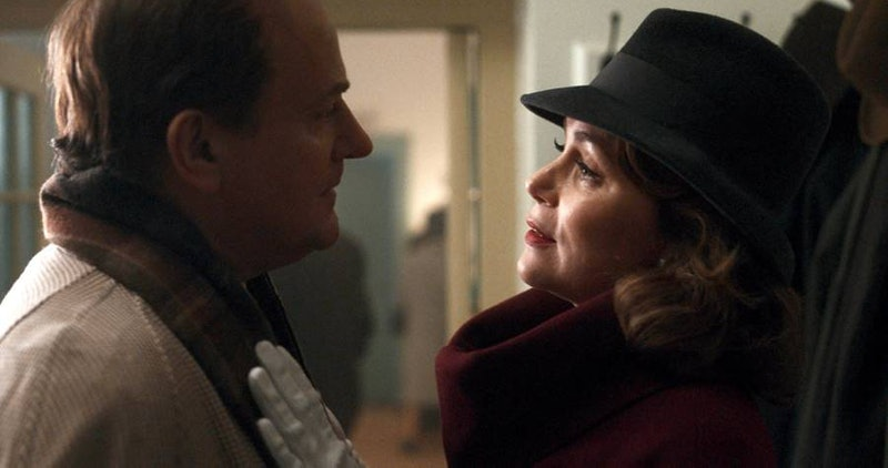 Hugh Bonneville as Roald Dahl and Keeley Hawes as Patricia Neal. Both are dressed in period clothing with Bonnville wearing a beige coat and brown-checked scarf and Hawes with her white-gloved hand on his chest wearing a black fedora hat and wine red cowl-neck coat