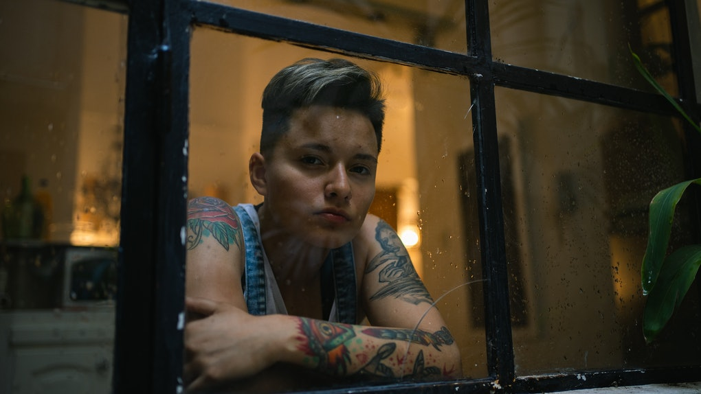 Young woman with tattoos looking out window