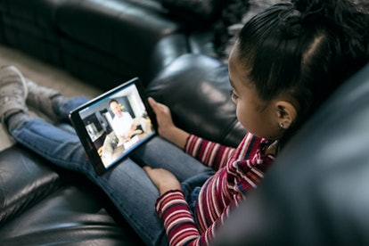A little girl is seen from above. She sits on a couch, looking down at a tablet, where a grown-up is looking back at her.
