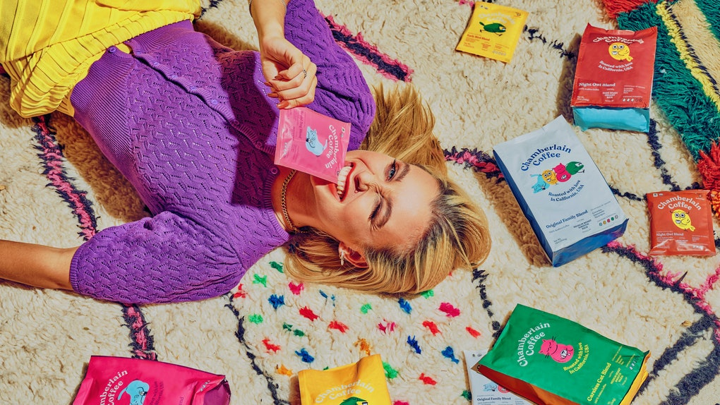 Emma Chamberlain lays amongst the Chamberlain Coffee products on a colorful rug.