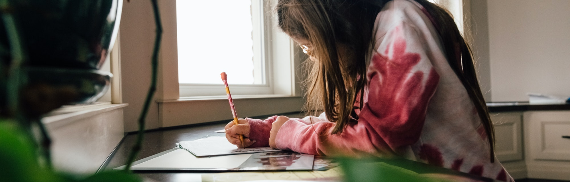Pre-teen girl with brunette hair is working on school work in the kitchen at home. Girl is wearing glasses and tie dyed sweatshirt.
