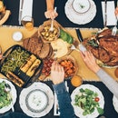 Everyone gathered around a Thanksgiving meal at the dinner table.