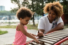 A mother and daughter playing outside.