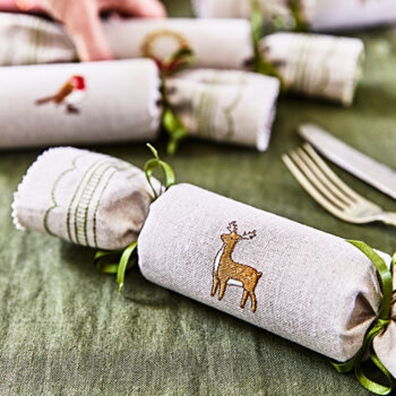 A  selection of christmas crackers covered in beige linen with embroidered deer and robin, on a green table cloth