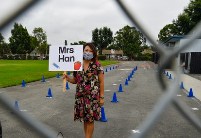 "Kindergarten teacher Suzi Han greets students at Weaver Elementary School on the first day of in-person learning. SHe is seen through a wire fence, holding a sign that says ""Mrs. Han"""