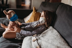 A little girl sits on her couch at home with a stuffed bunny; they are both wearing face masks.