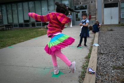 "A little girl twirls around on the sidewalk outside her school, during a ""mask break"" from Kindergarten class."