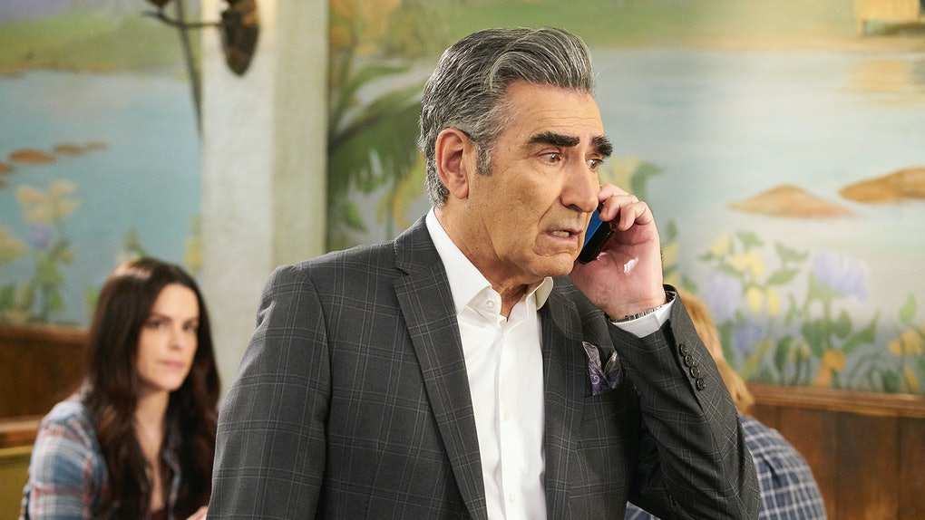 Johnny Rose (Eugene Levy) talks on the phone while standing in a restaurant on 'Schitt's Creek.'