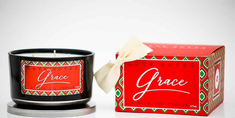 """A three-wick candle with """"grace"""" printed in white on red backing sits next to a gift box with a white bow and the same label. Doing your holiday shopping with Black-owned wellness businesses is a great way to get all your holiday needs met."""