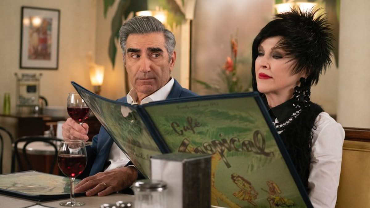 Johnny Rose (Eugene Levy) looks over at Moira Rose (Catherine O'Hara) while sitting at the Cafe Trop...
